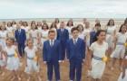 Dutzende von Kindern haben sich auf dem Strand versammelt: ihr Gesang ist ergreifend