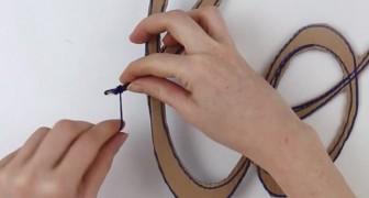 Hon flätar en ylletråd på en kartong: det blir ett jättefint föremål som ni kan inreda hemmet med!