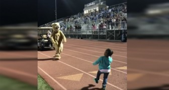 A little girl dances with a mascot in the stadium!