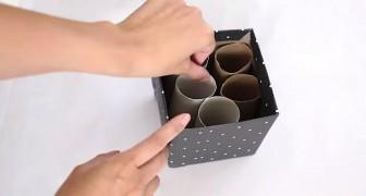 Sie stellt Papprollen in eine alte Schachtel.. Ihre Idee ist nützlich!