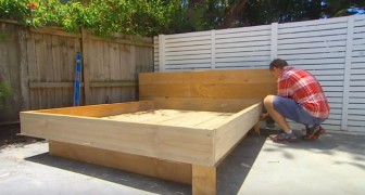 Een man bouwt een bed in de tuin... met een heel bijzonder matras!
