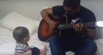 Il papà suona la chitarra... il piccolo reagisce nel più esilarante dei modi