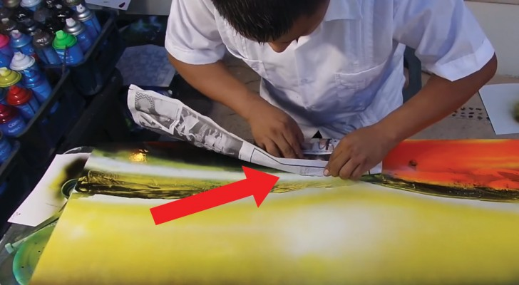 Colori spray, carta di giornale e fuoco: scoprite il risultato finale di questa misteriosa opera
