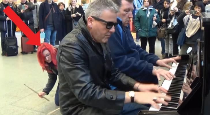 Deux hommes divertissent le public en jouant du piano, mais regardez bien la jeune femme aux cheveux roux
