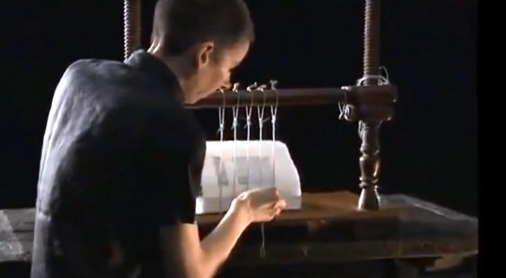 Een man naait vellen papier aan elkaar om een kwalitatief hoogwaardig product te creëren