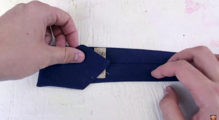 Hij begint een stropdas op te vouwen... het eindresultaat is een vleugje STIJL!