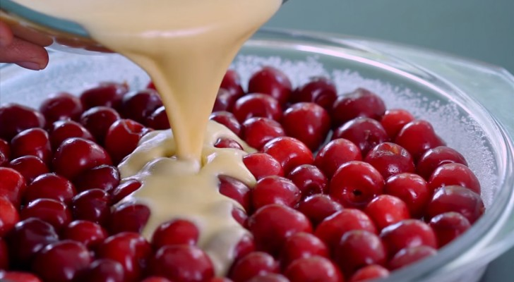 Il verse le mélange sur les cerises fraîches et crée un dessert à la saveur délicate et irrésistible